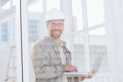 Smiling male architect using laptop in office Stock Photo