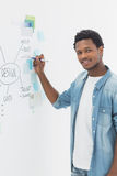 Smiling male artist with pen in front of whiteboard Stock Images