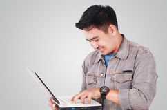 Smiling Male Asian Student Typing on Laptop. Photo image portrait of a cute young Asian male student standing and smiling while holding laptop and typing on it Stock Images