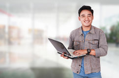 Smiling Male Asian Student Typing on Laptop. Photo image portrait of a cute young Asian male student standing and smiling while holding laptop and typing on it Stock Photography