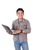 Smiling Male Asian Student Typing on Laptop. Photo image portrait of a cute young Asian male student standing and smiling while holding laptop and typing on it Stock Photo