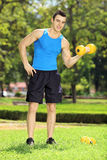 Smiling male athlete exercising with weight in a park Stock Image