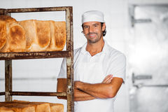 Smiling Male Baker Standing Arms Crossed By Bread Rack Royalty Free Stock Images