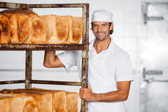 Smiling Male Baker Standing By Bread Rack Royalty Free Stock Photography
