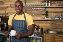 Smiling male barista holding coffee cup in cafe. Portrait of smiling male barista holding coffee cup in cafe Stock Image