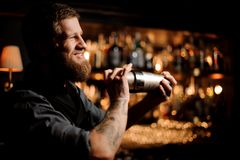 Male bartender uses shaker to prepare an alcohol cocktail. Smiling male bartender uses steel shaker to prepare an alcohol cocktail royalty free stock photos