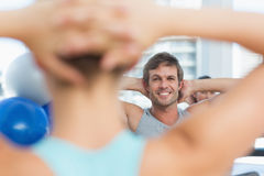 Smiling male with blurred people doing stretching exercises Stock Photos