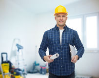 Smiling male builder in helmet with blueprint Royalty Free Stock Photos