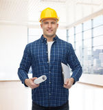 Smiling male builder in helmet with blueprint Stock Photography