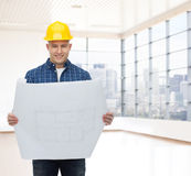 Smiling male builder in helmet with blueprint. Repair, construction, building, people and maintenance concept - smiling male builder or manual worker in helmet Royalty Free Stock Photo