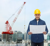 Smiling male builder in helmet with blueprint. Repair, construction, building, people and maintenance concept - smiling male builder or manual worker in helmet Royalty Free Stock Image