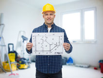 Smiling male builder in helmet with blueprint Royalty Free Stock Images