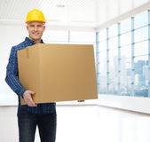 Smiling male builder in helmet with cardboard box Royalty Free Stock Photography