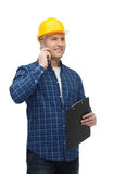 Smiling male builder in helmet with clipboard. Construction, building, people, technology and maintenance concept - smiling male builder or manual worker in Stock Photography