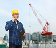 Smiling male builder in helmet with clipboard. Construction, building, people, technology and maintenance concept - smiling male builder or manual worker in Stock Photos