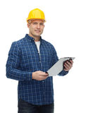 Smiling male builder in helmet with clipboard Royalty Free Stock Images