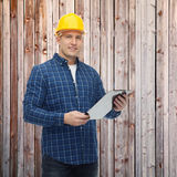 Smiling male builder in helmet with clipboard Stock Photography