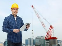 Smiling male builder in helmet with clipboard Stock Photo
