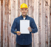 Smiling male builder in helmet with clipboard Royalty Free Stock Image