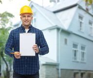 Smiling male builder in helmet with clipboard Royalty Free Stock Photography