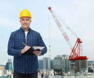 Smiling male builder in helmet with clipboard Stock Photos