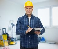 Smiling male builder in helmet with clipboard Stock Images