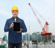 Smiling male builder in helmet with tablet pc Stock Photos