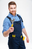 Smiling male builder holding wrench. Isolated on a white background Royalty Free Stock Photos