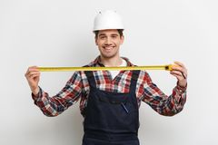 Smiling male builder in protective helmet showing measuring tape. And looking at the camera over grey background Royalty Free Stock Photography