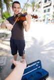 Smiling male busker playing violin Stock Photo