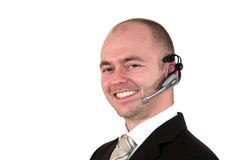 Smiling male call center agent. A smiling male call center agent with  a headset, isolated on white background Royalty Free Stock Images