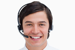 Smiling male call center agent with headset on. Close up of smiling male call center agent with headset on against a white background Stock Photo