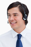Smiling male call center agent looking to the side. Close up of smiling male call center agent looking to the side against a white background Stock Photography