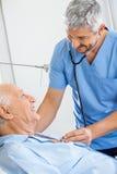 Smiling Male Caretaker Examining Senior Man Stock Photo