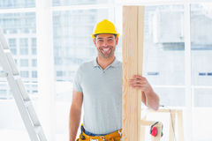Smiling male carpenter holding plank in building Stock Photos