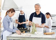 Smiling Male Chef With Colleagues Preparing Pasta Stock Photos