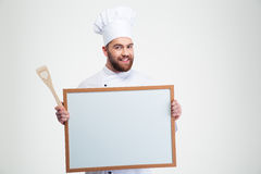 Smiling male chef cook holding blank board. Portrait of a smiling male chef cook holding blank board isolated on a white background Stock Photos