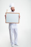 Smiling male chef cook holding blank. Full length portrait of a smiling male chef cook holding blank board isolated on a white background Stock Photos
