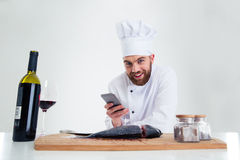 Smiling male chef cook using smarpthone Stock Images