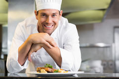 Smiling male chef with cooked food in kitchen. Portrait of a smiling male chef with cooked food standing in the kitchen Royalty Free Stock Images