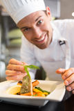 Smiling male chef garnishing food in kitchen Royalty Free Stock Photography