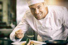 Smiling male chef garnishing food in kitchen Stock Photos
