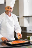 Smiling male chef garnishing food in kitchen Royalty Free Stock Photos