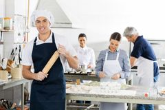 Smiling Male Chef Holding Rolling Pin While Royalty Free Stock Photos