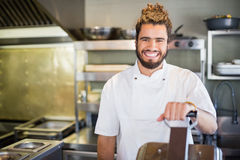 Smiling male chef standing in commercial kitchen. Portrait of smiling male chef standing in commercial kitchen royalty free stock image