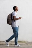 Smiling male college student walking with bag and mobile phone. Full body side portrait of a smiling male college student walking with bag and mobile phone Royalty Free Stock Image