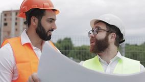 Smiling male construction engineer discussion with architect at construction site or building site of highrise building. They holding construction drawings in stock footage