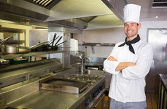 Smiling male cook with arms crossed in the kitchen. Portrait of a smiling male cook with arms crossed standing in the kitchen Royalty Free Stock Photos