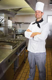 Smiling male cook with arms crossed in the kitchen Stock Image