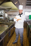 Smiling male cook with arms crossed in the kitchen Royalty Free Stock Images